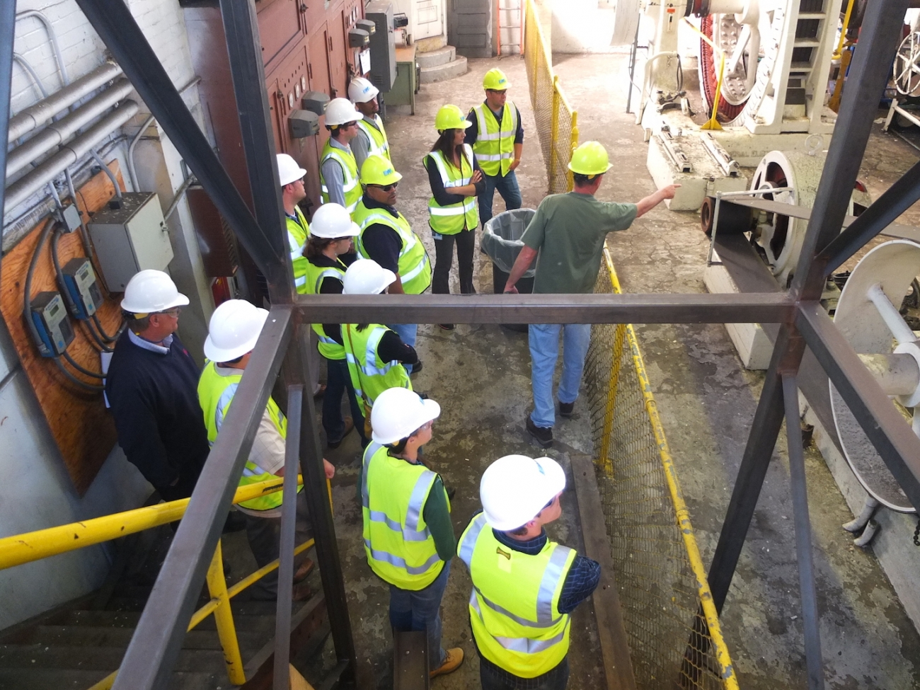 A group of interns wearing BWL uniforms and hard hats listens as an employee teaches them about machinery.