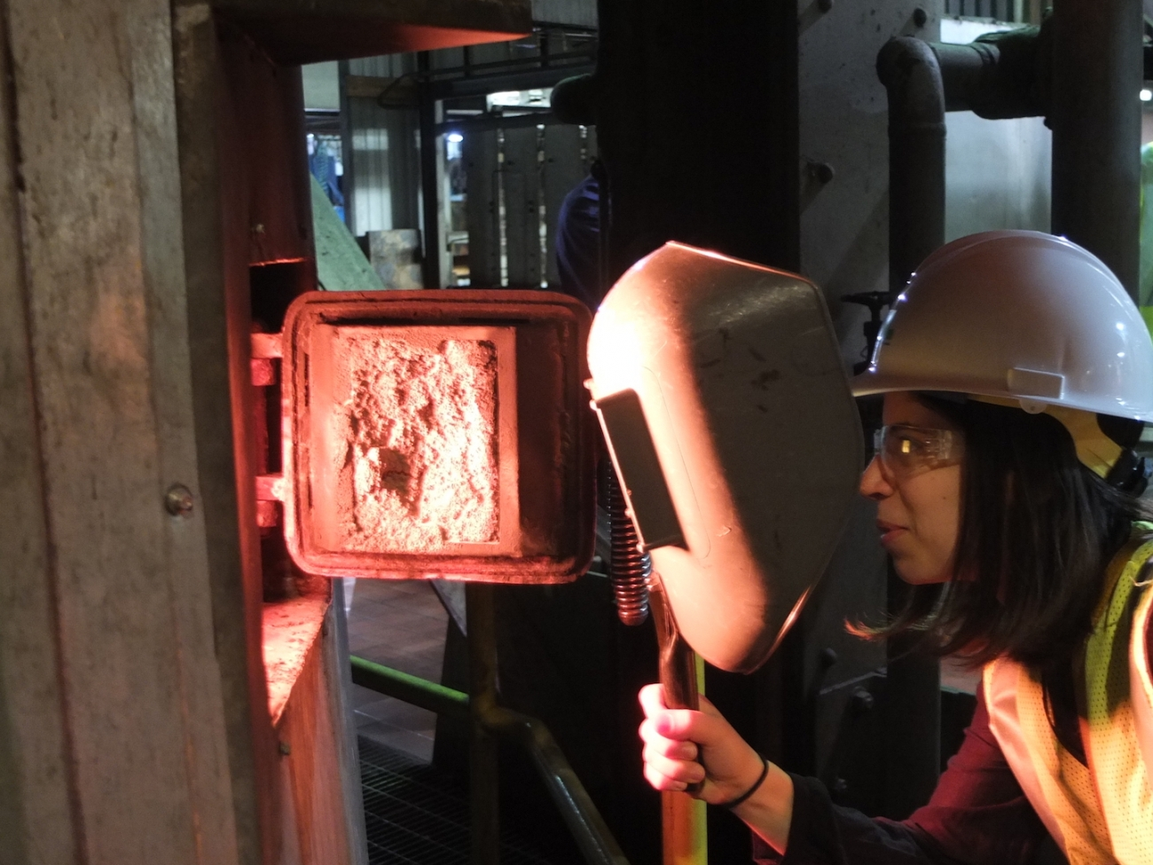 An intern peers into a furnace.